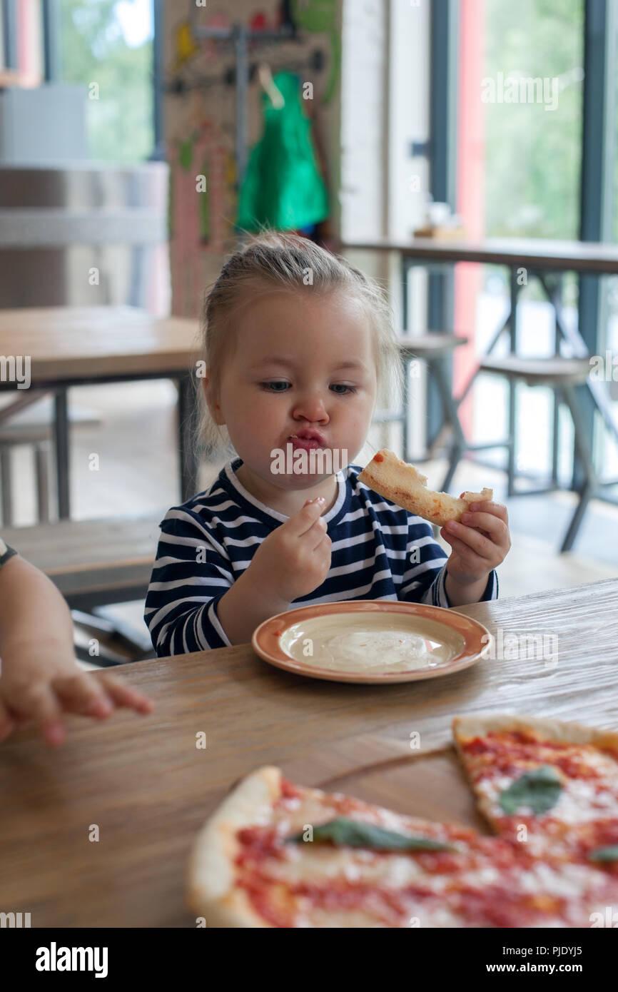 Süße kleine lustige 2 Jahre Mädchen essen Pizza im Restaurant Stockbild