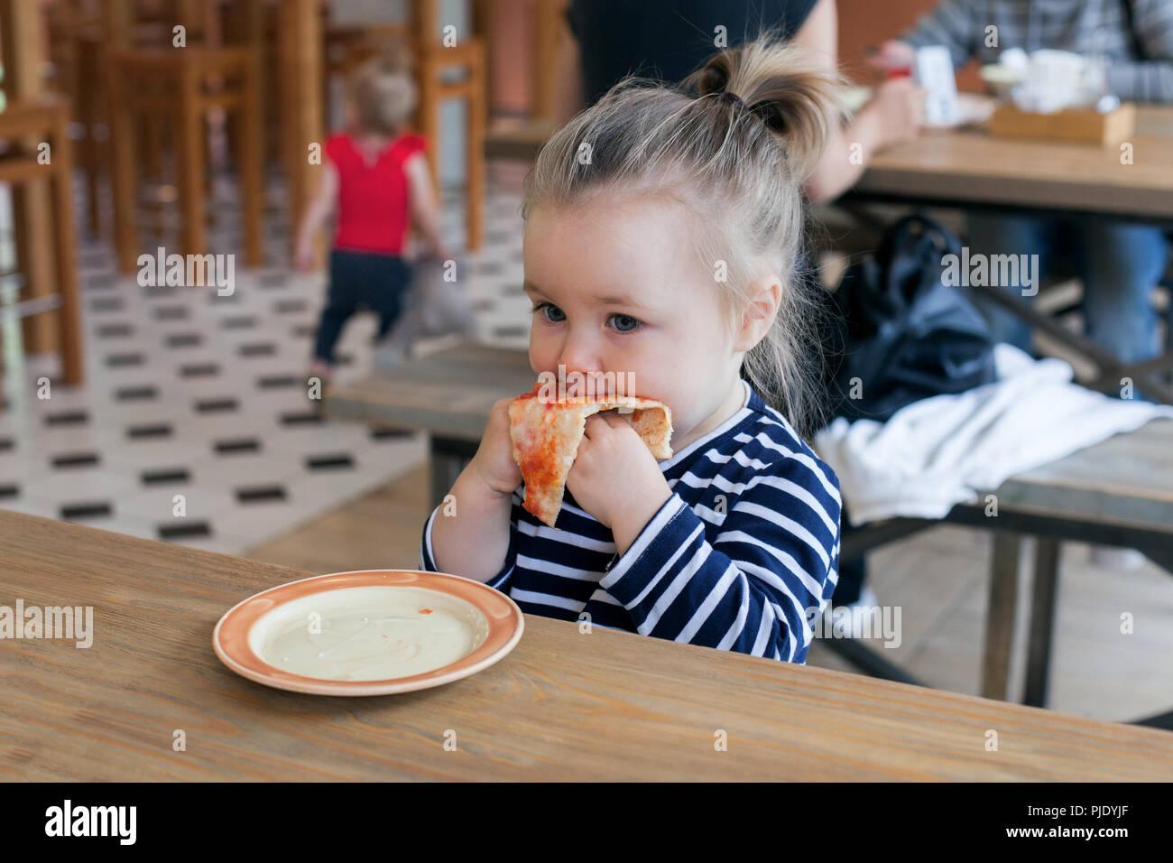 Süße kleine 2 Jahre Mädchen essen Pizza im Restaurant Stockbild