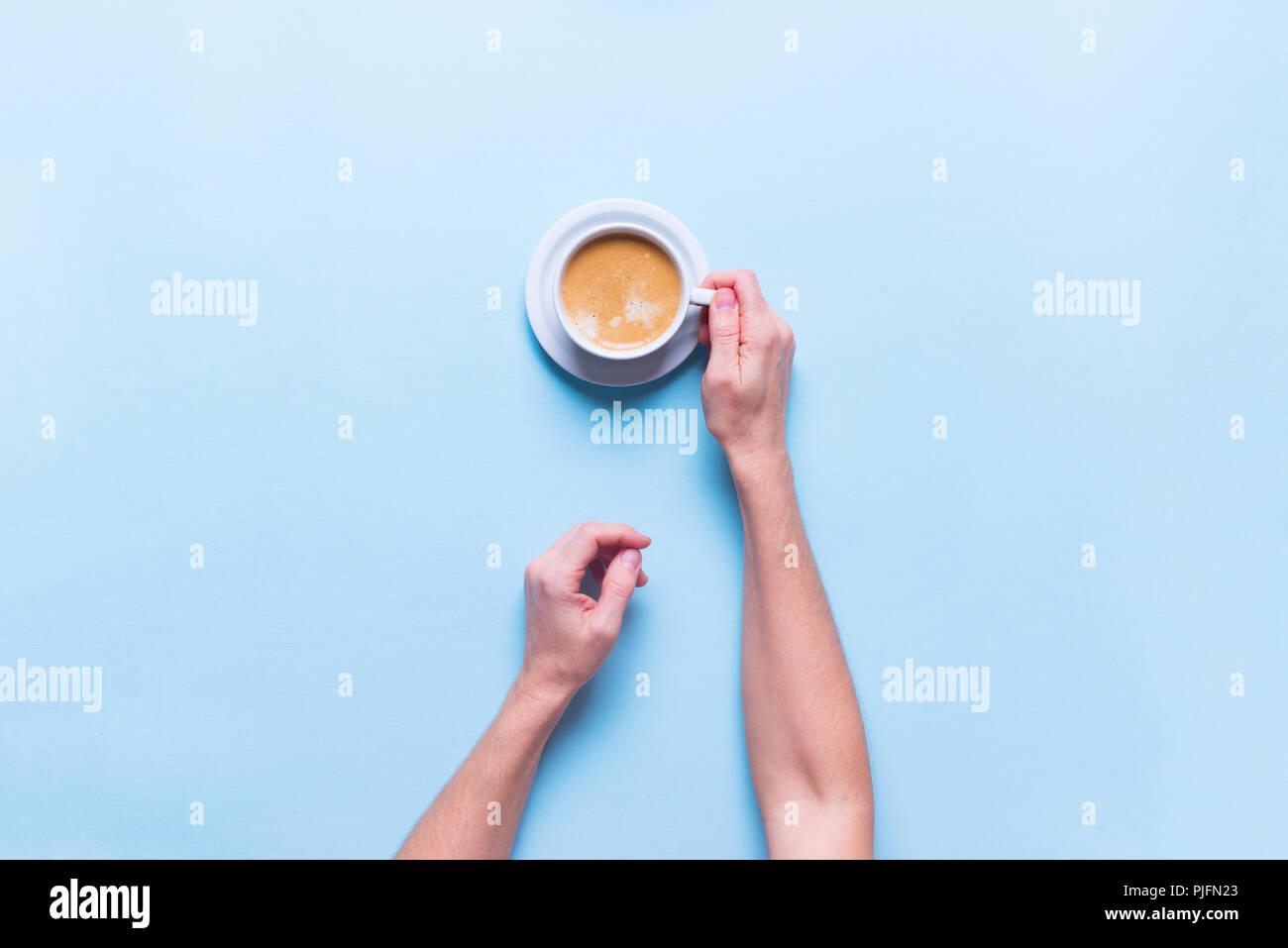 Weibliche Hände hält frische Tasse Kaffee Farbe blau Hintergrund der Ansicht von oben Flach ungesunde Nahrung ein Objekt Stockbild