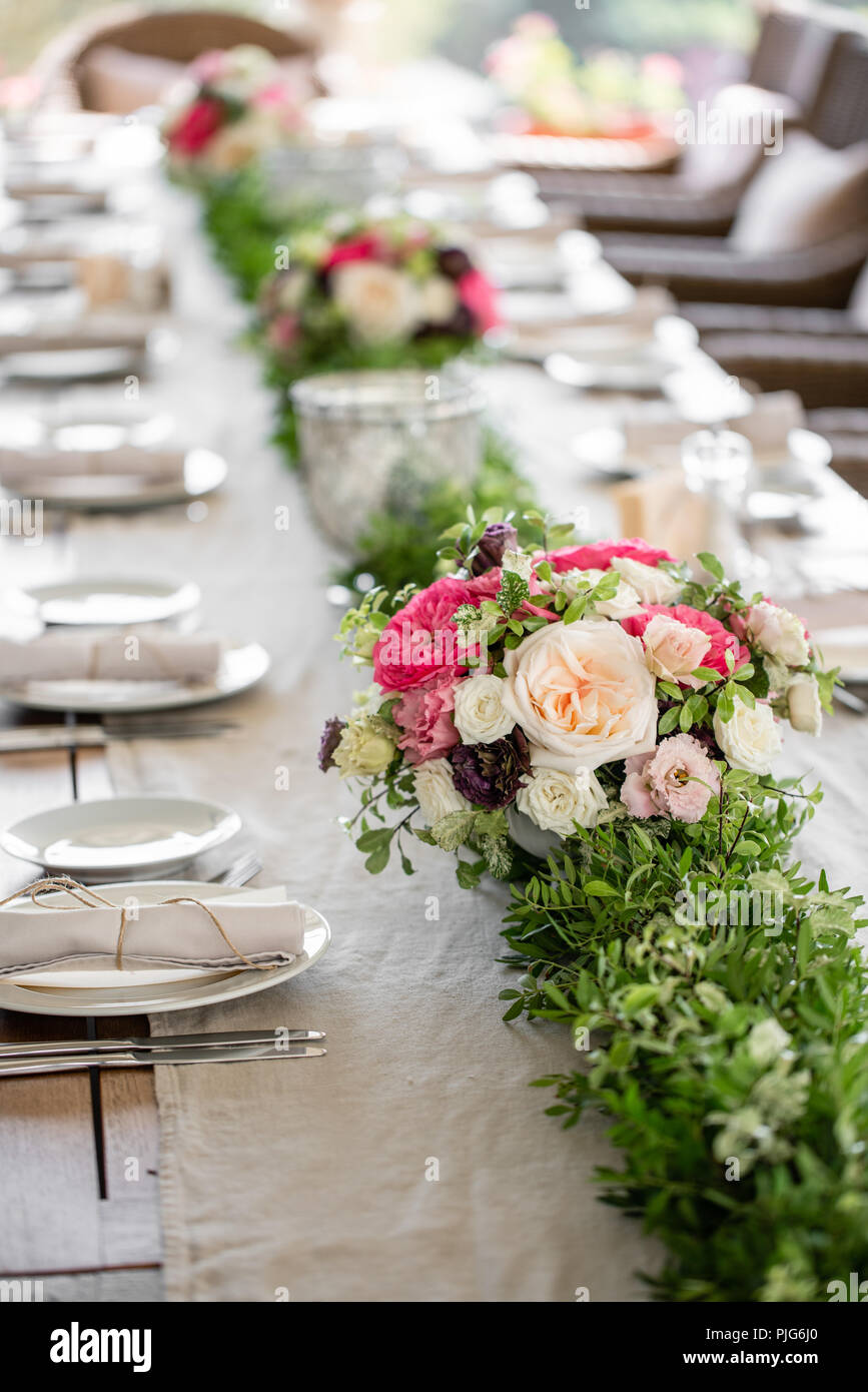 Hochzeit oder Gala Dinner. Die Tische und Stühle für Gäste, serviert mit Besteck und Geschirr. Mit einem Leinen Tischdecke Läufer abgedeckt. Party auf der Terrasse Stockbild