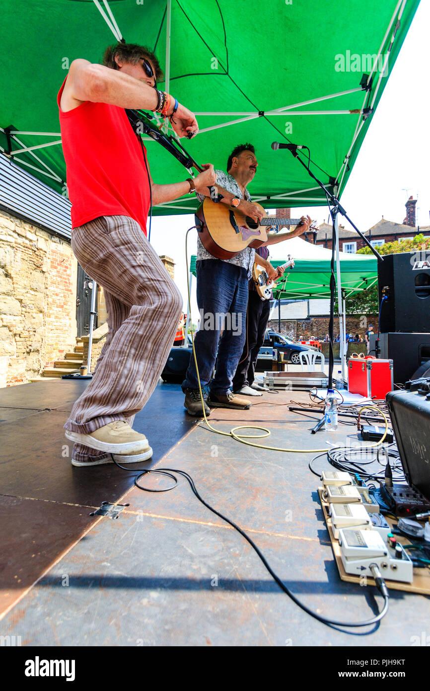 Die heiße Ratten auf einer kleinen offenen Bühne während das Sandwich Folk und Ale-Veranstaltung. Seite Blick entlang der Bühne, Violine Spieler mit zwei Gitarristen hinter sich. Stockbild