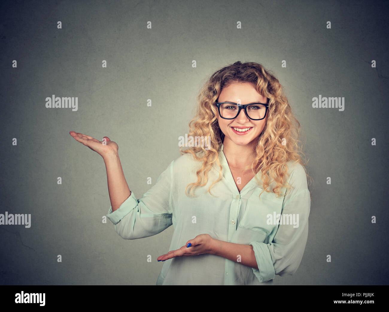 Junge Frau in Brillen zeigen und die Präsentation auf grauem Hintergrund Stockbild