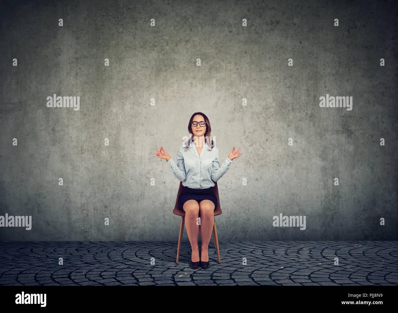 Business Woman in Gläsern sitzen auf einem Stuhl und halten sich an den Händen auseinander in Meditation und Harmonie halten die Augen geschlossen. Stockbild