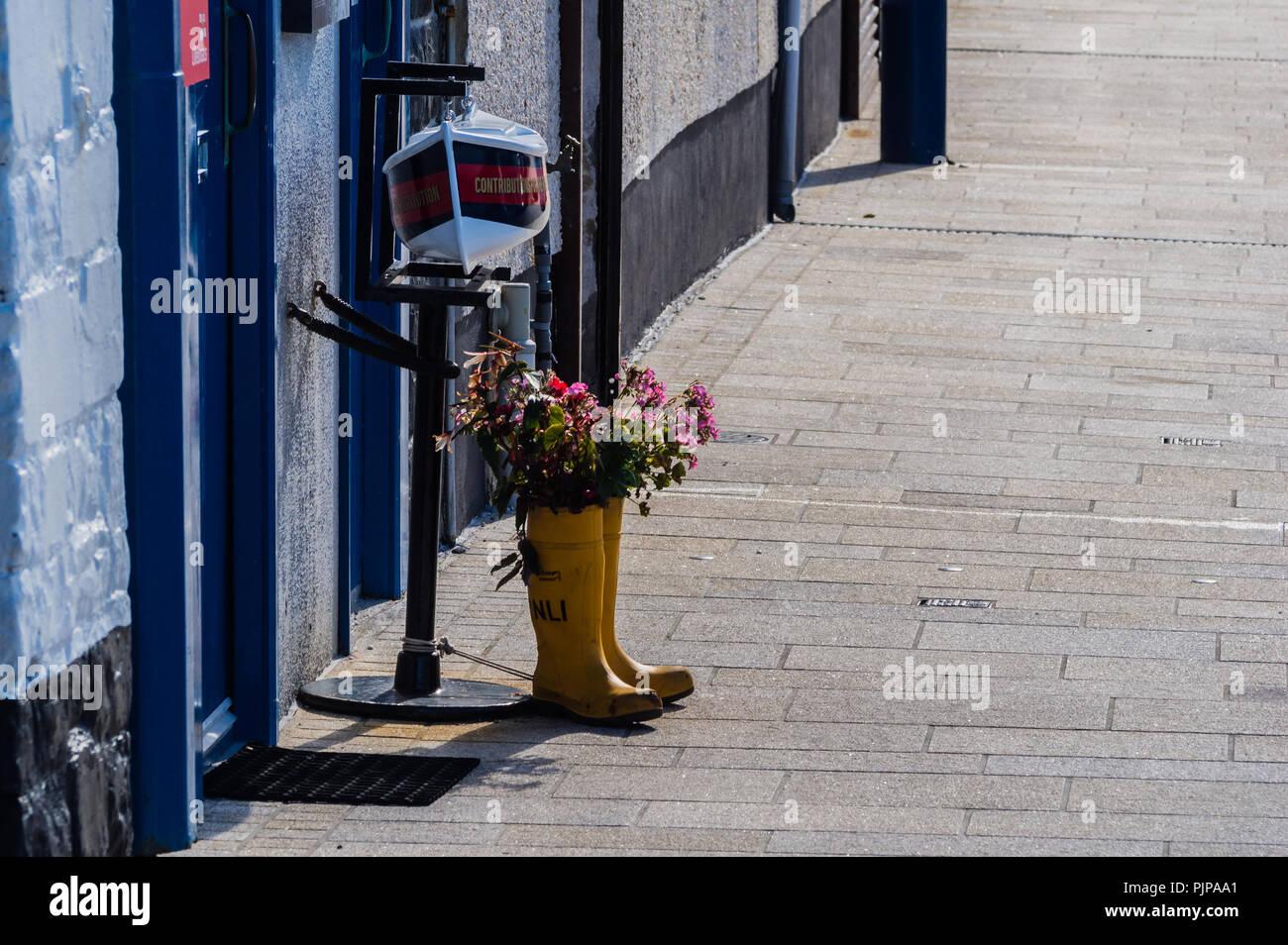 Alte RNLI Wellingtons upcycled als Blume Pflanzmaschinen außerhalb der RNLI-Station in Donaghadee Stockbild