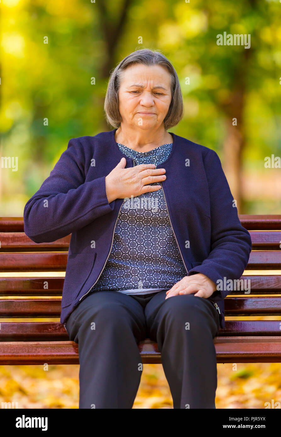 Ältere Dame umklammerte ihre Brust Schmerzen bei den ersten Anzeichen von Angina pectoris oder Myokardinfarkt oder Herzinfarkt, Oberkörper im Park an einem Herbsttag Stockbild