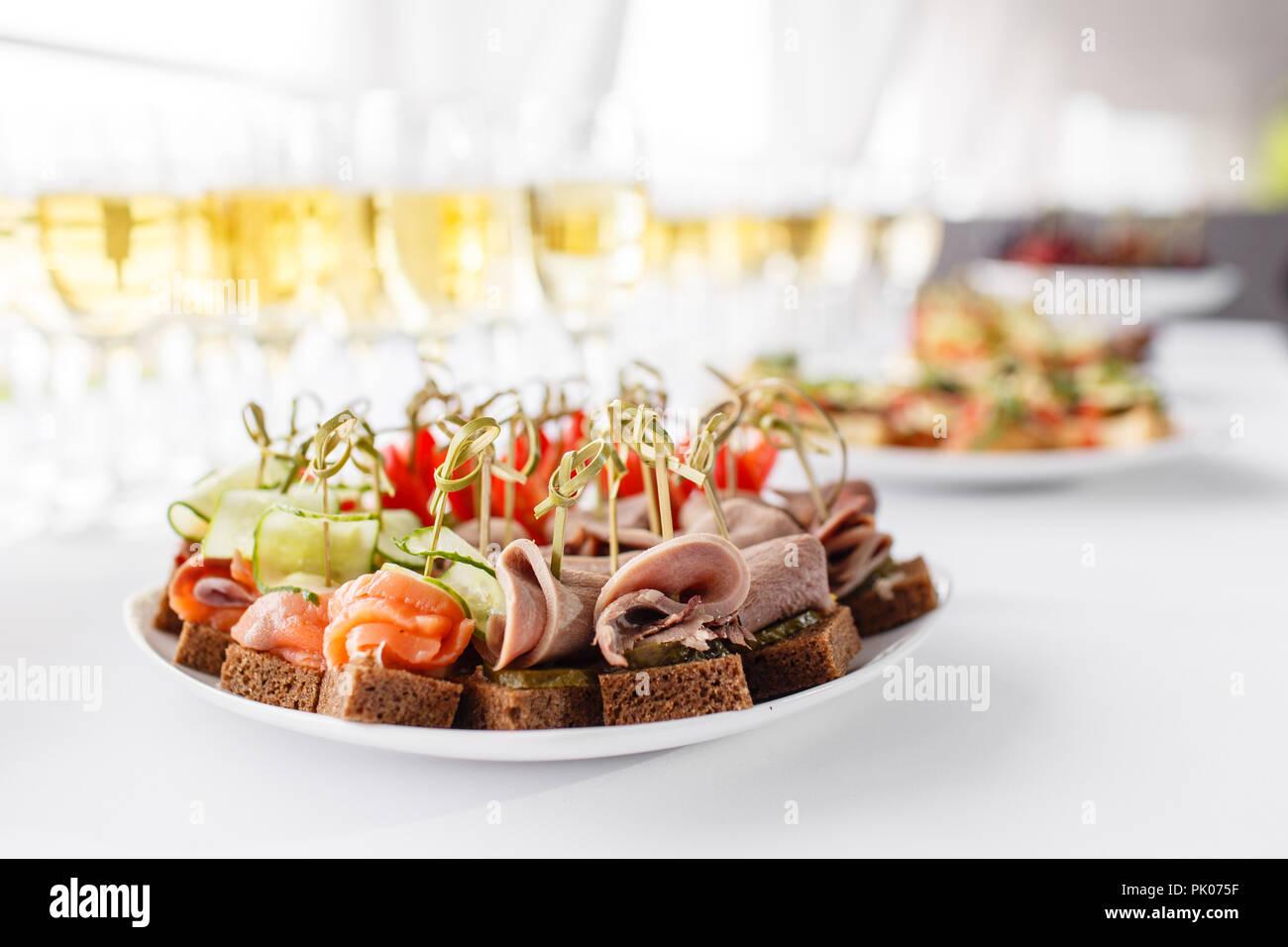 Roggen Brot Sandwiches, Kanapees, Bruschetta auf weiße Platte. feierlichen Bankett. Viele Gläser Champagner oder Wein auf dem Tisch im Restaurant Buffet mit vielen leckeren Snacks. Stockbild
