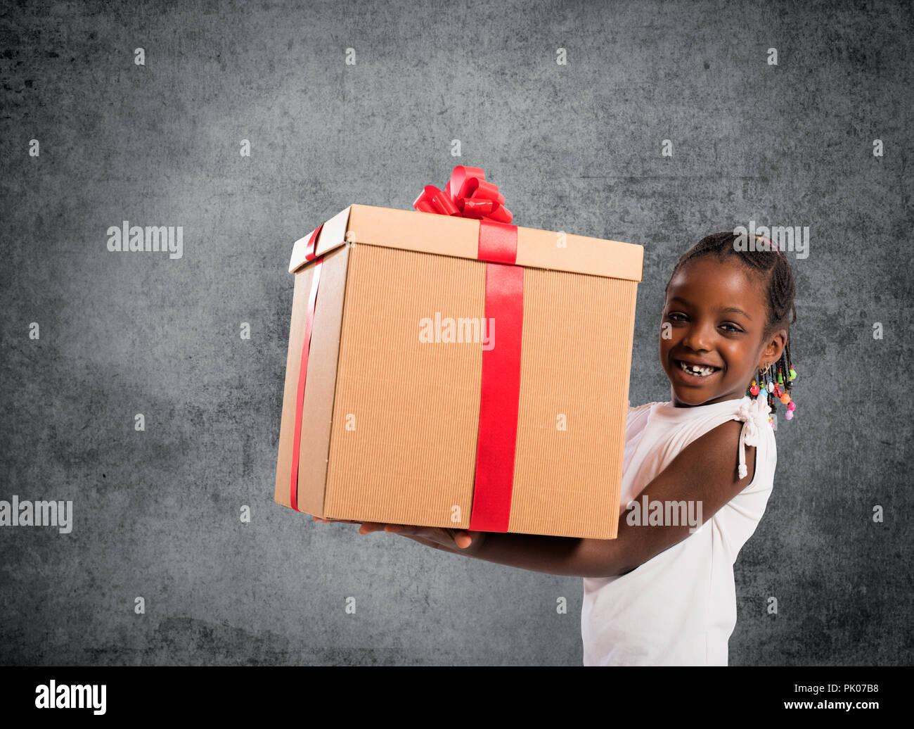 Glückliches kleines Mädchen mit einem Weihnachtsgeschenk Stockfoto ...