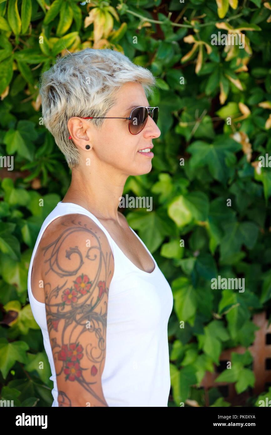 blonde frau mit blumen tattoos auf dem arm stockfoto bild. Black Bedroom Furniture Sets. Home Design Ideas
