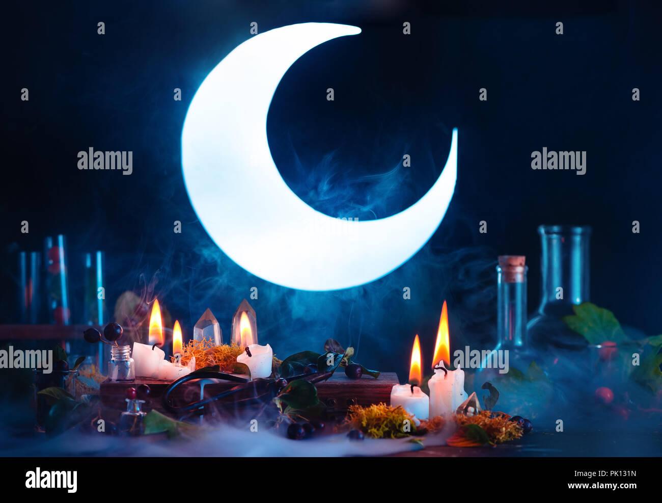 Halloween Header mit strahlenden Vollmond. Hexe oder Zauberer Arbeitsplatz mit brennenden Kerzen. Gespenstisch still life Konzept auf einem dunklen Hintergrund mit Kopie spac Stockbild