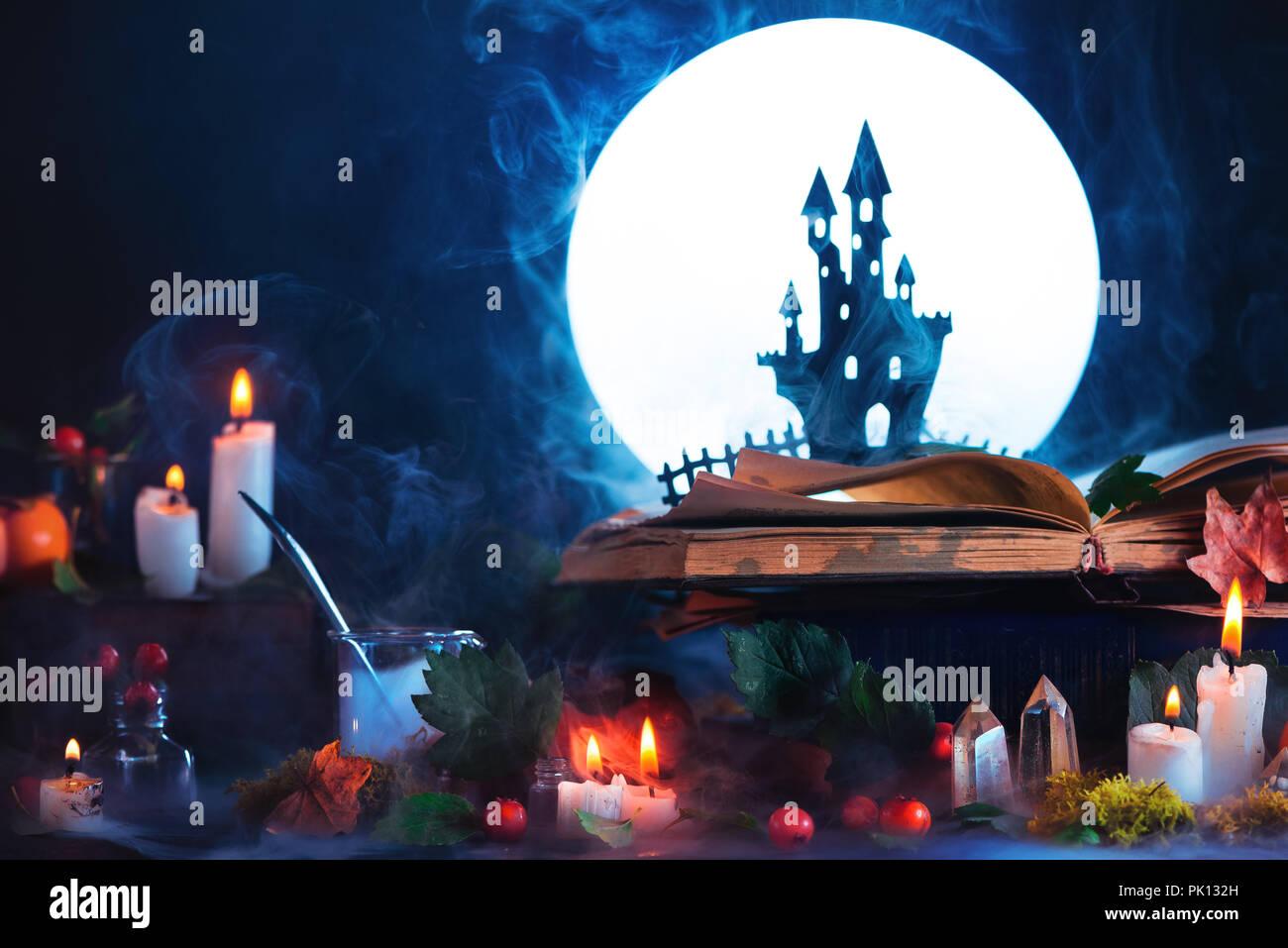 Halloween Konzept mit einem spukschloss Silhouette vor Vollmond. Das Buch der Zaubersprüche auf Hexe oder Zauberer Arbeitsplatz. Kreative magisch noch Leben auf Stockbild