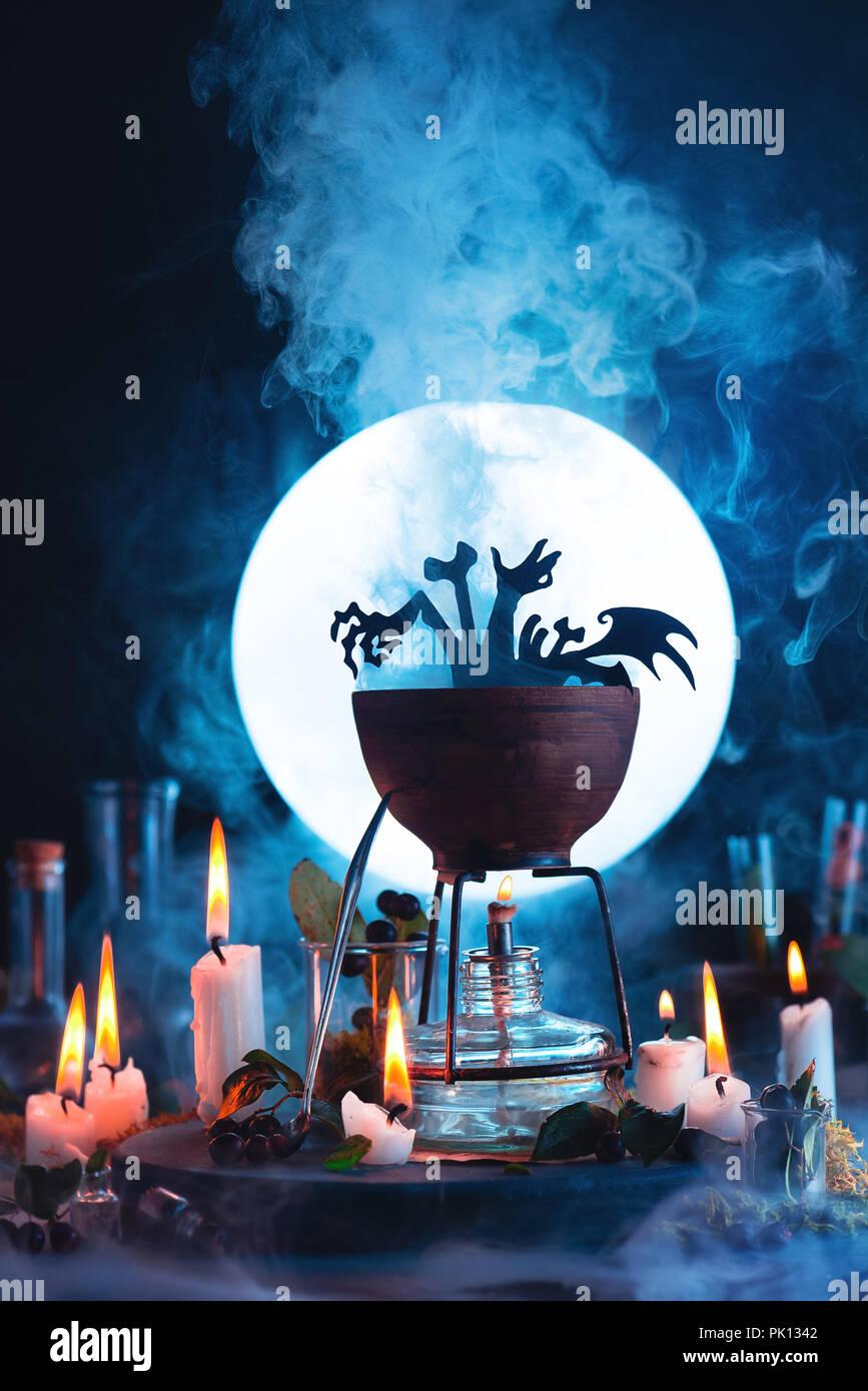 Halloween-Konzept mit einem Kessel Silhouette vor Vollmond. Magischen trank mit aufsteigenden Dampf auf Hexe oder Zauberer Arbeitsplatz. Konzeptionelle noch li Stockbild