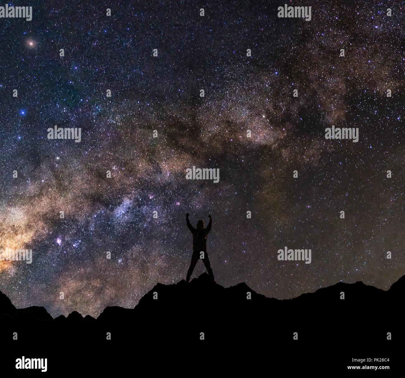 Silhouette einer glücklichen Mann mit erhobenen Armen zu Milchstraße Hintergrund Stockfoto