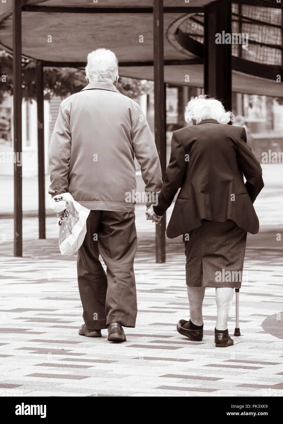 Ansicht der Rückseite des ältere Paare halten sich an den Händen. Großbritannien Stockbild