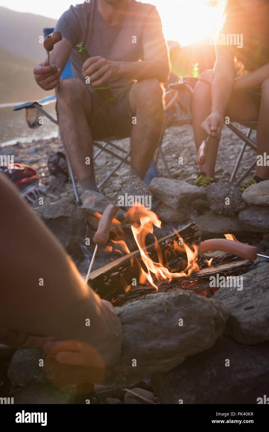 Gruppe von Freunden am Lagerfeuer rösten Hot Dogs. Stockfoto