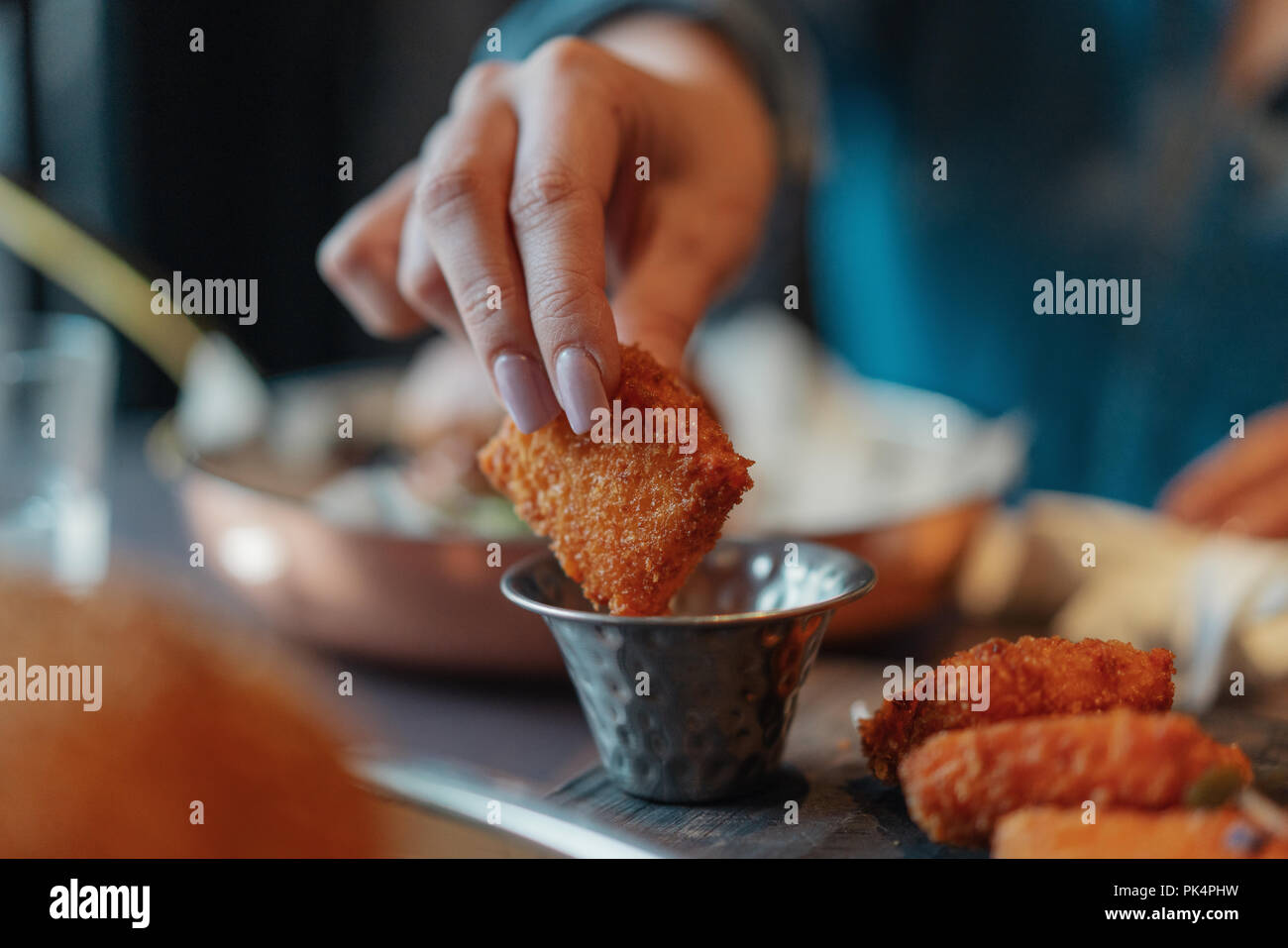 Nahaufnahme von Frau Hände halten gebratener Käse und tauchen Sie in eine Soße. Stockbild