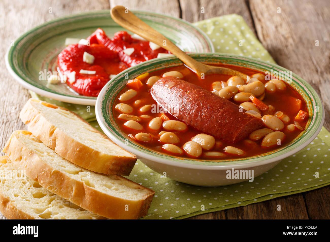 Landhausstil, Pasulj (grah) Bohnensuppe mit Wurst mit Brot und marinierte Paprika closeup auf einem Teller auf den Tisch serviert. Horizontale Stockbild