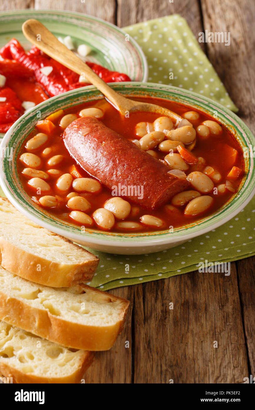 Köstliche pasulj Bohnensuppe mit Wurst mit eingelegten Pfeffer und Brot in der Nähe serviert - auf den Tisch. Vertikale Stockbild
