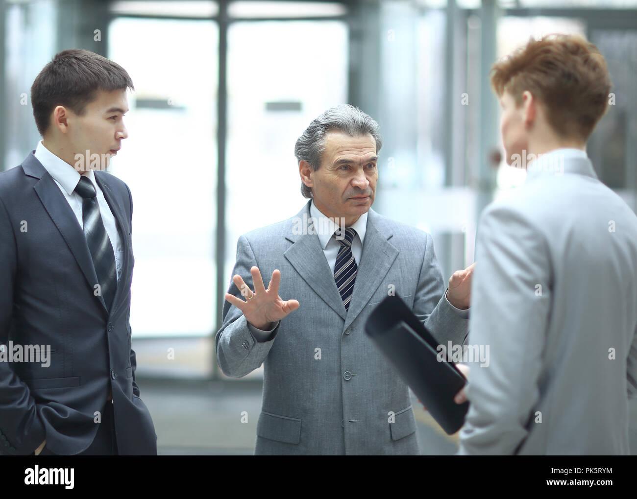 Strenge Chef im Gespräch mit einem Mitarbeiter. Foto auf unscharfen Büro Hintergrund Stockbild
