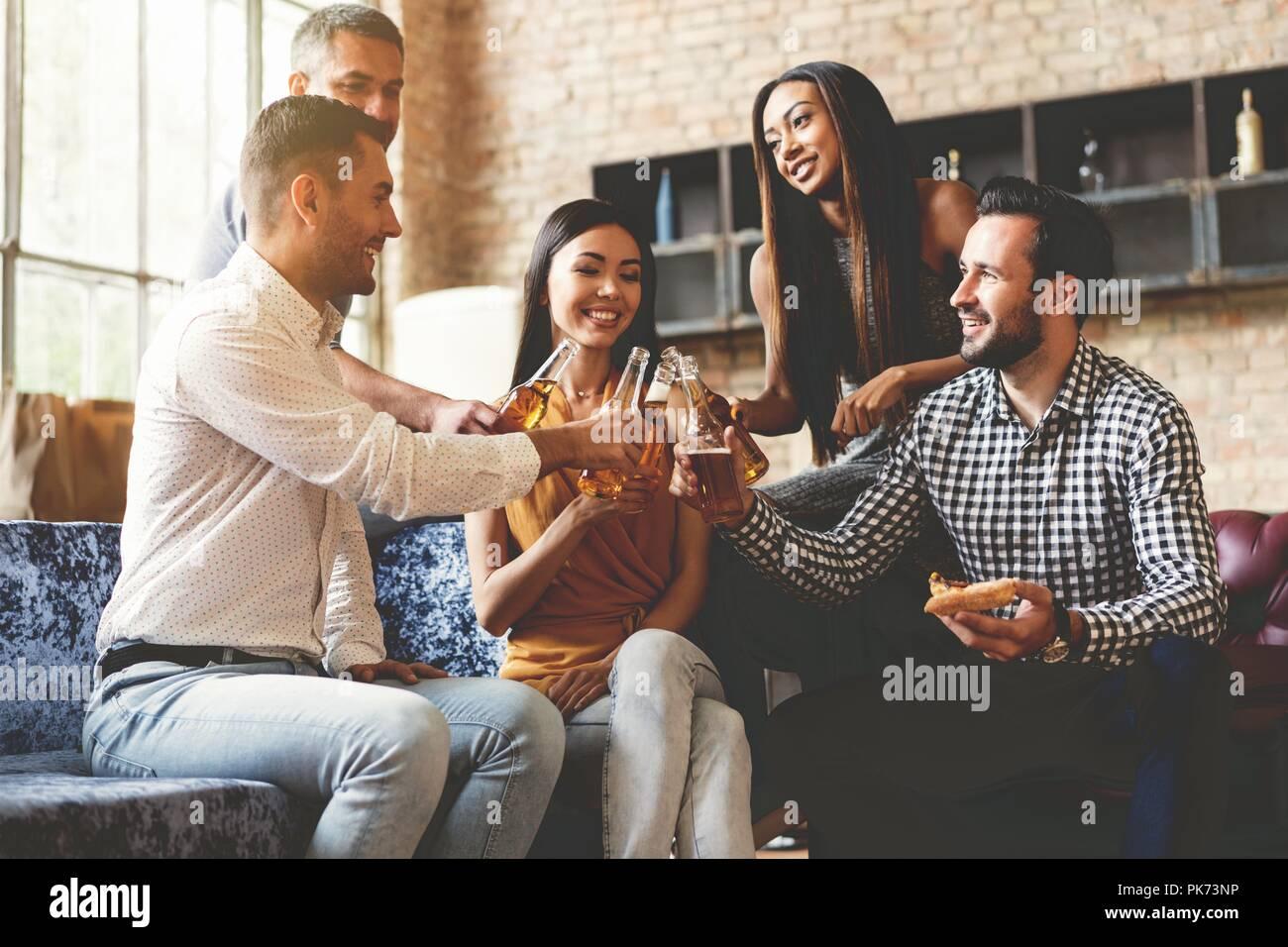 Verbringen eine tolle Zeit mit den besten Freunden. Gruppe von fröhlichen jungen Menschen genießen Sie Speisen und Getränke während der schönen Zeit in Cofortable Stühle in der Küche zusammen. Stockbild