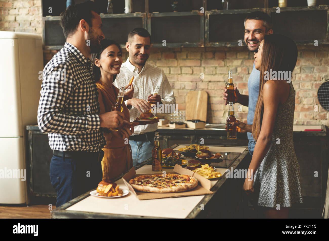 Home Party. Volle Länge des fröhlichen jungen Menschen genießen Home Party während der Kommunikation und essen Snacks auf der Küche. Stockbild