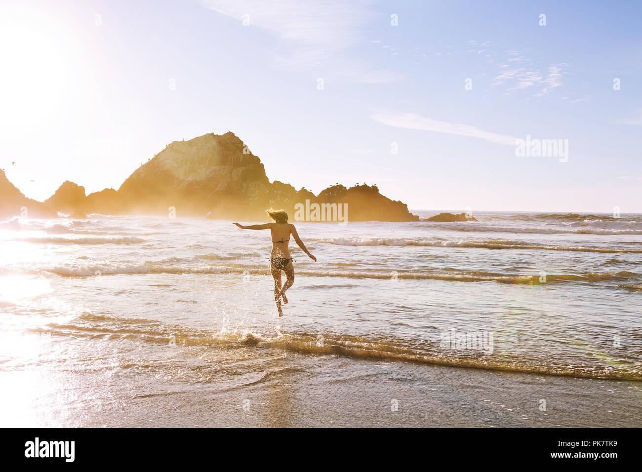 Frau läuft in den Pazifischen Ozean Stockbild