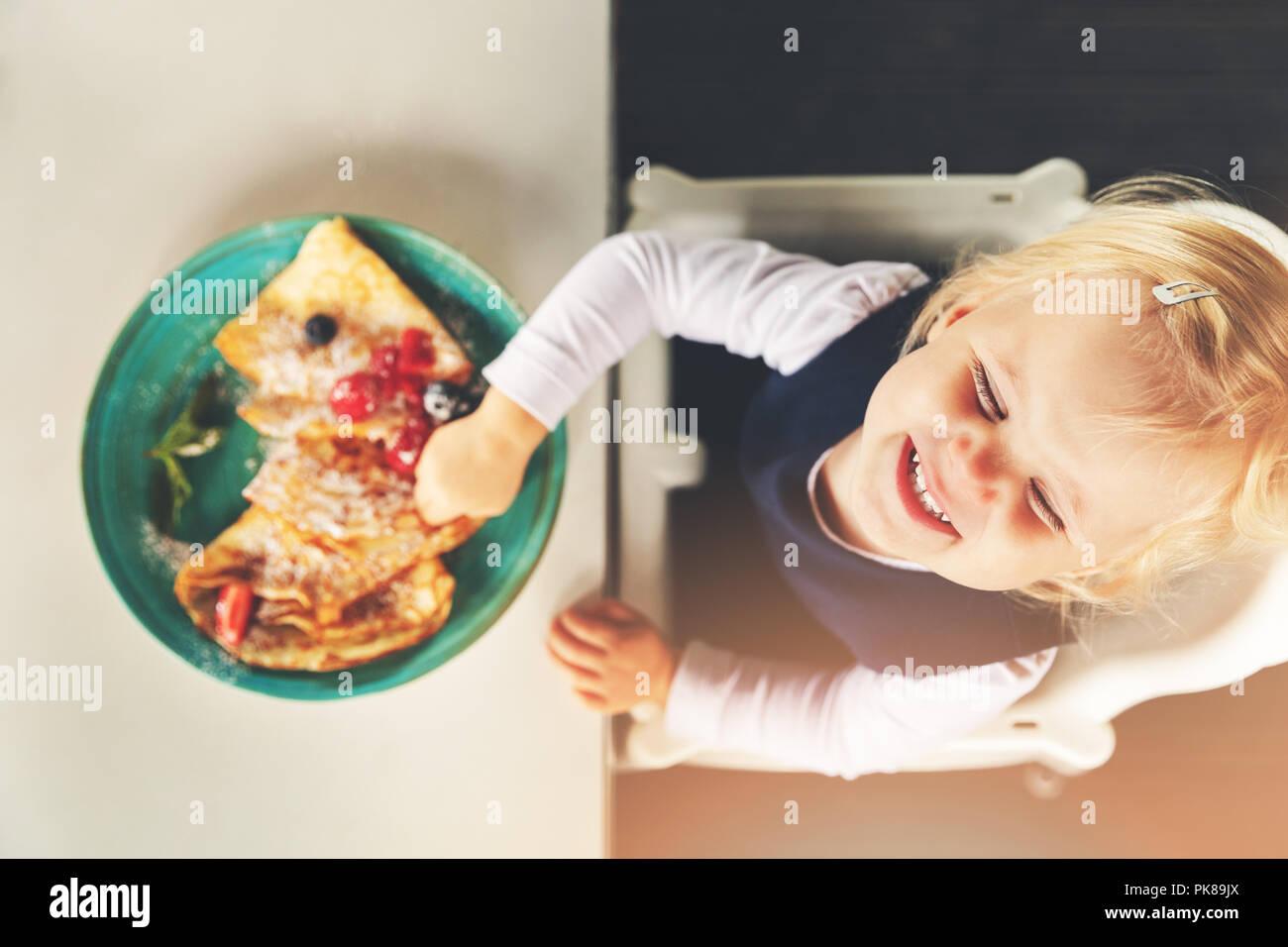 Nette lustige kleine Mädchen essen Pfannkuchen mit Beeren Stockbild
