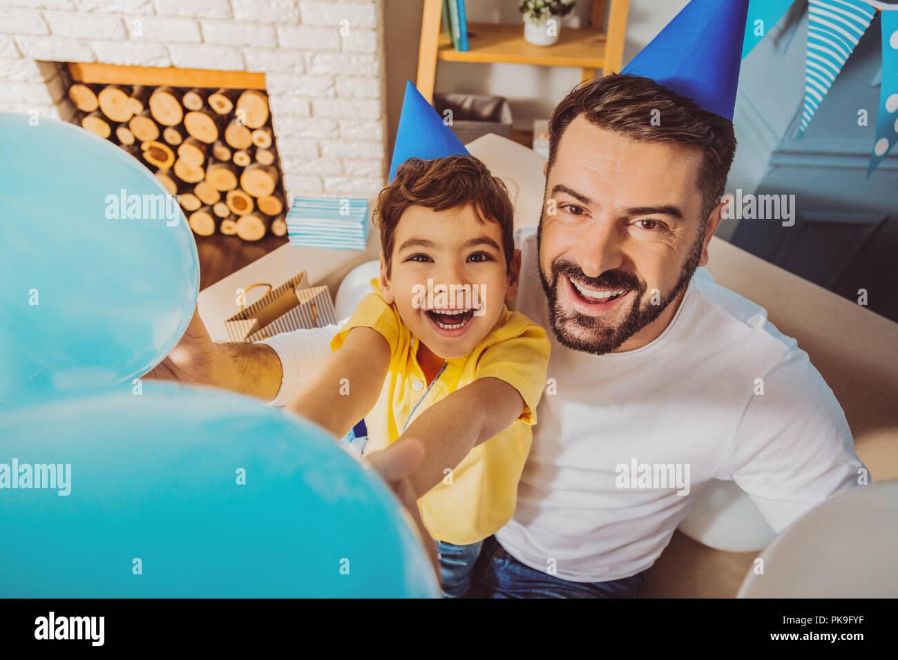 Hübscher netter Mann und Junge spielt mit Ballons Stockbild