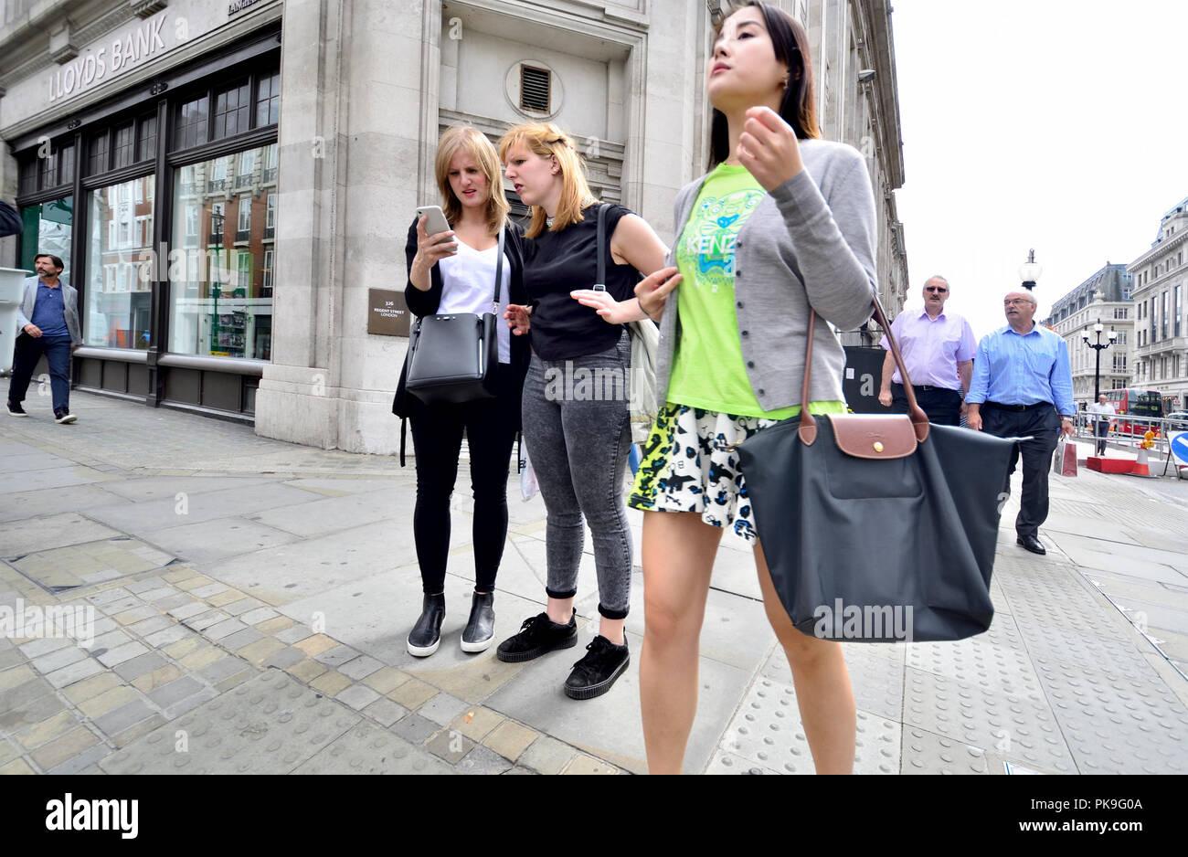 Zwei junge Frauen auf einem Mobiltelefon suchen, Regent Street, London, England, UK. Stockbild
