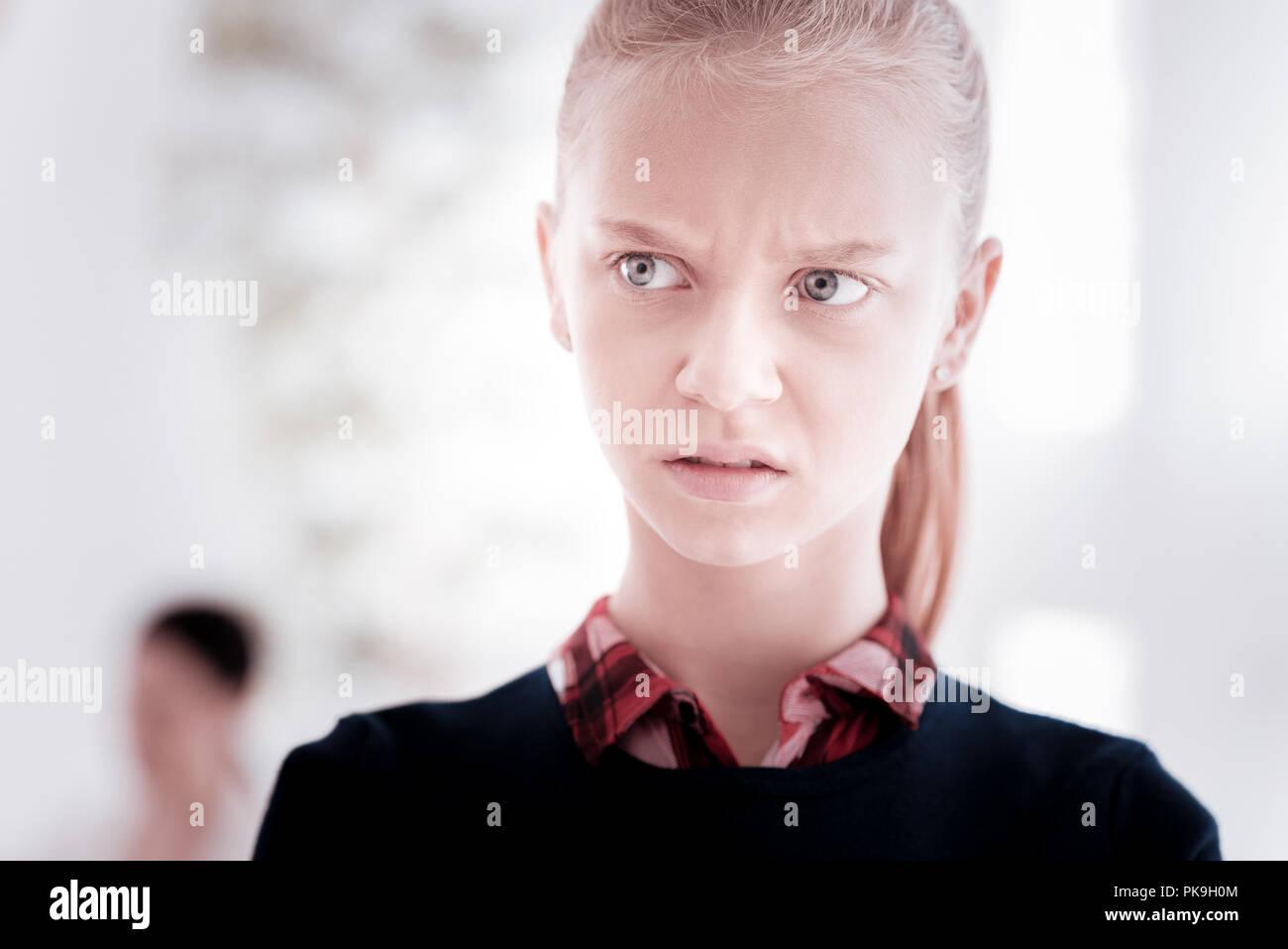 Emotionale Mädchen runzelte die Stirn und unwohl in einem fremden Ort Stockfoto