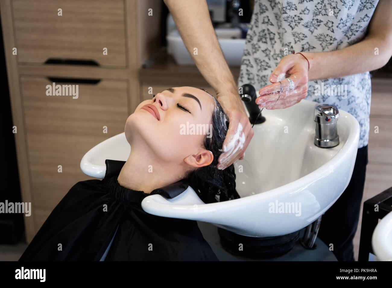 Friseur. Schöne brünette Frau während der Haare waschen Stockbild