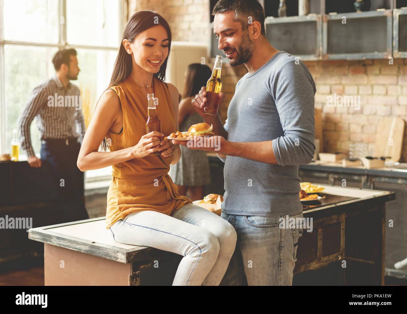 Party mit den besten Freunden. Gruppe von fröhlichen jungen Menschen genießen Home Party mit Snacks und Getränken während der Kommunikation auf die Küche. Stockbild