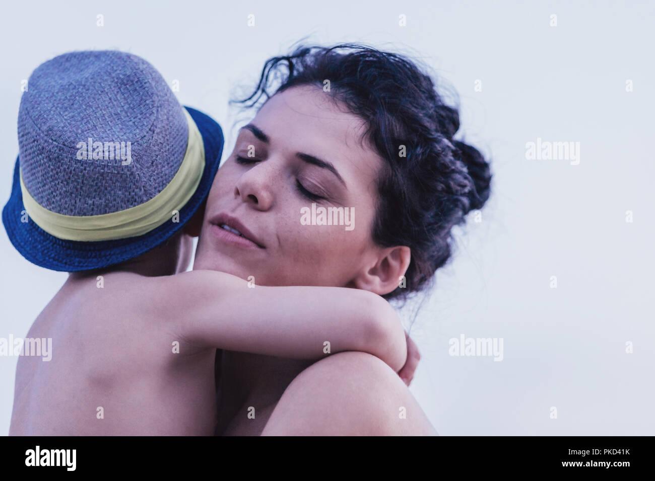 Glückliche Mutter mit ihrem Sohn genießen Sie die schönen sonnigen Tag am Strand. Die Mutter ihren Sohn umarmen. Positiver menschlicher Emotionen, Gefühle, Freude. Glückliche Familie Stockbild