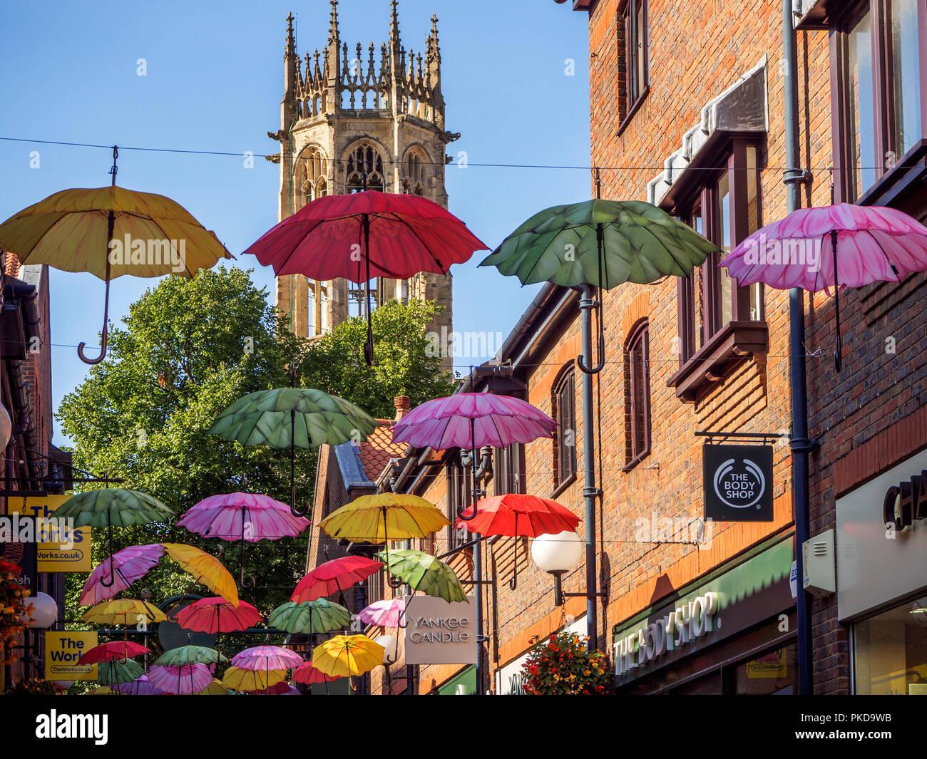 Bunte Sonnenschirme über Coppergate mit allen Heiligen Pflaster Kirchturm hinter York Yorkshire England Stockbild