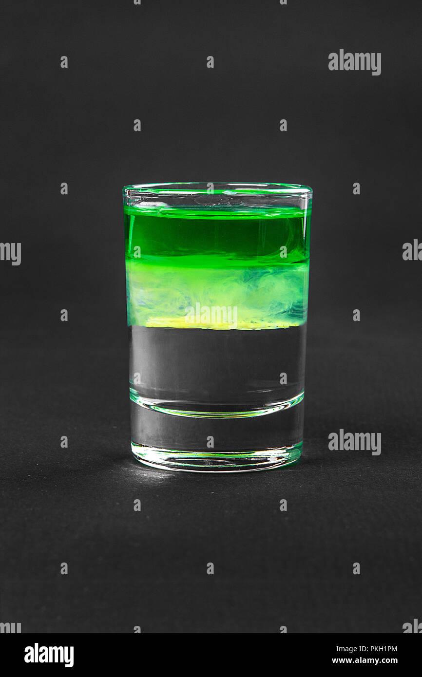 Mehrfarbig geschichtete Cocktail, Glas mit transparenten und farbigen Drink mit dem Geschmack der Minze, Banane, Zitrone, Absinth, alkoholische, Seitenansicht isoliert Stockbild