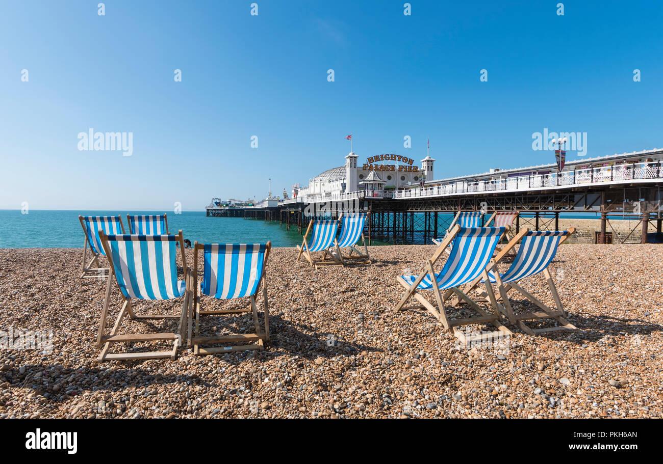Brighton Palace Pier, Leere Liegestühle und Strand im Sommer in Brighton Beach, Brighton, East Sussex, England, UK. Stockbild