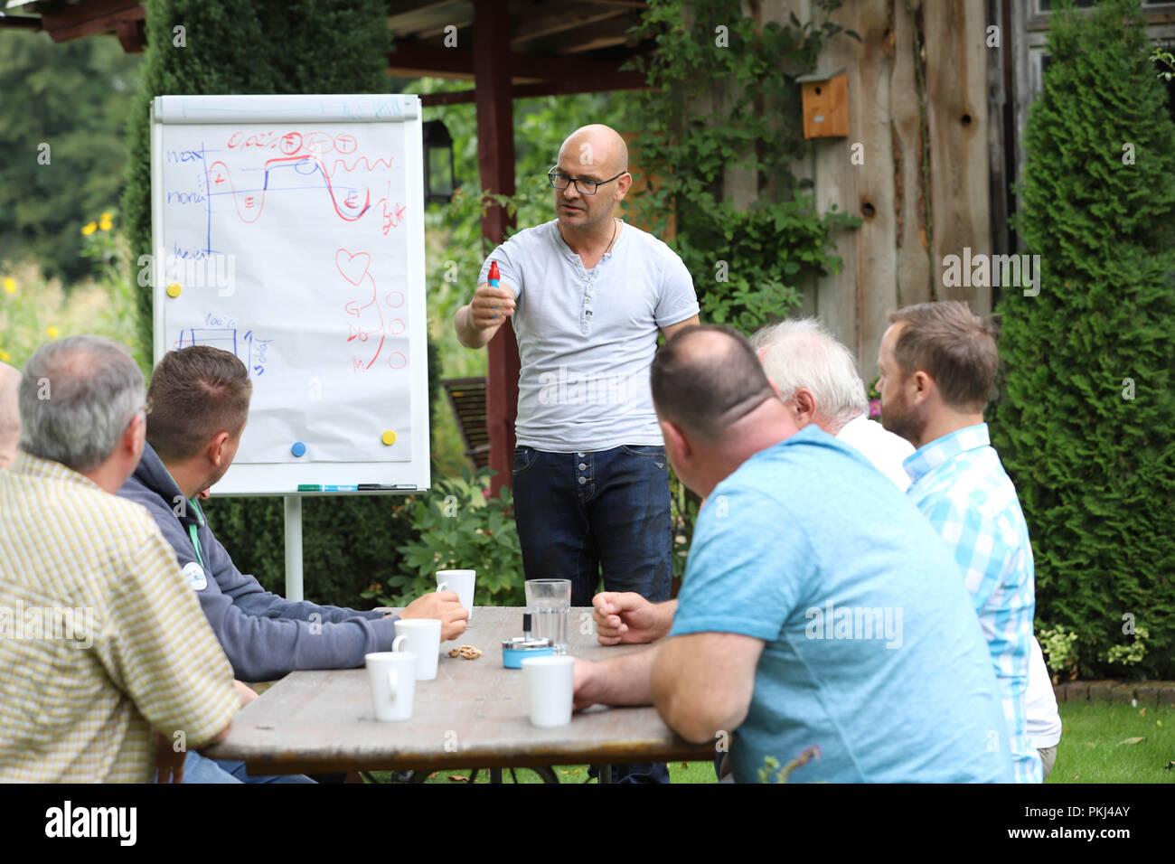 """Behavioral Trainer während einer Vorlesung zum Thema """"Stressmanagement"""" in einen sommerlichen Garten in Brandenburg/Deutschland. Stockfoto"""