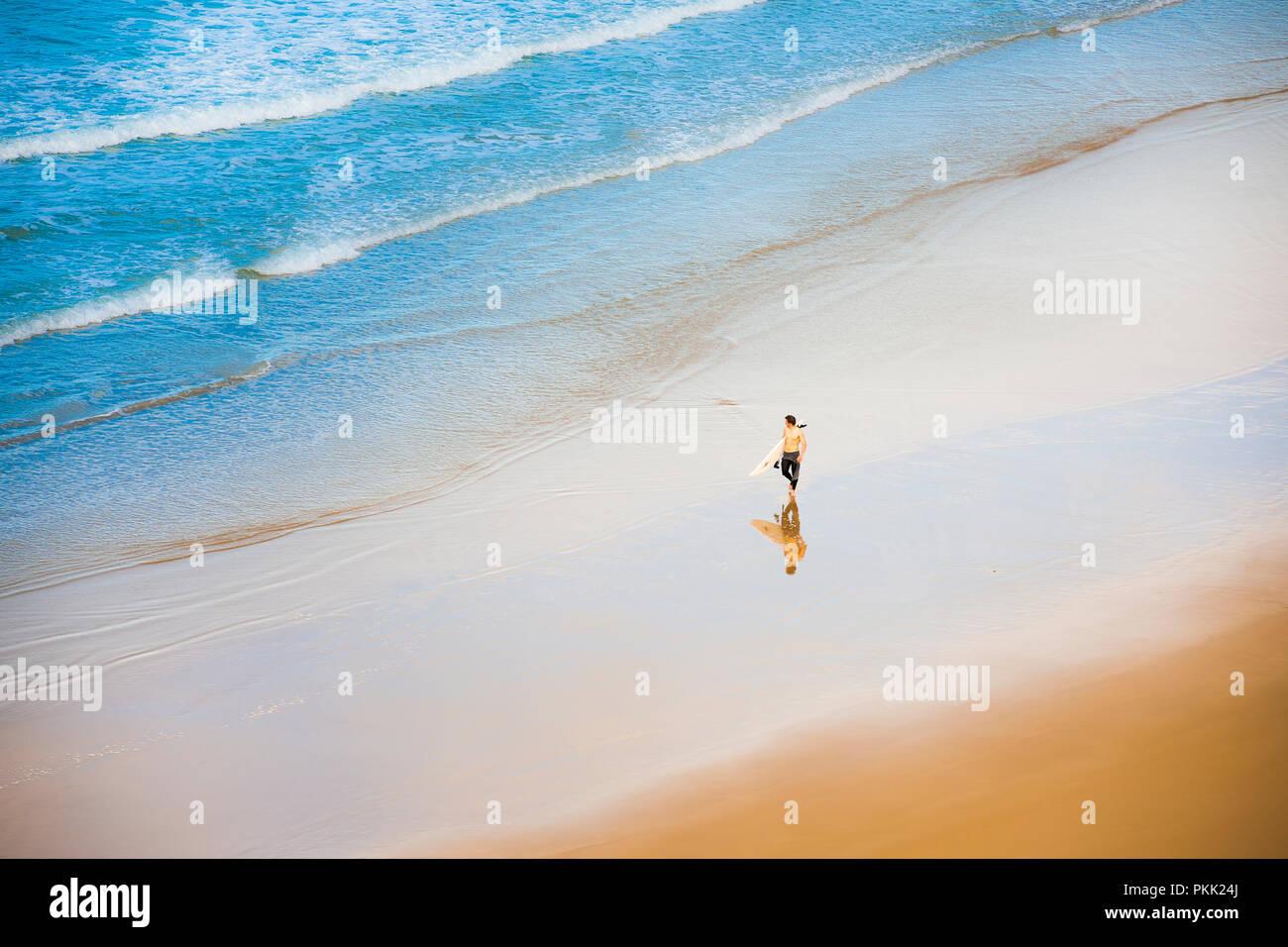 Surfer gehen entlang Sandstrand, von oben Stockbild