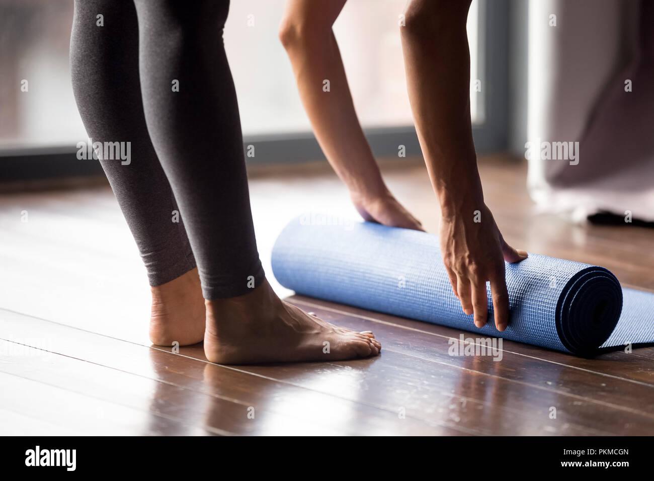 Mädchen rolling Yoga Matte für Meditation oder Fitness zu Hause Stockfoto