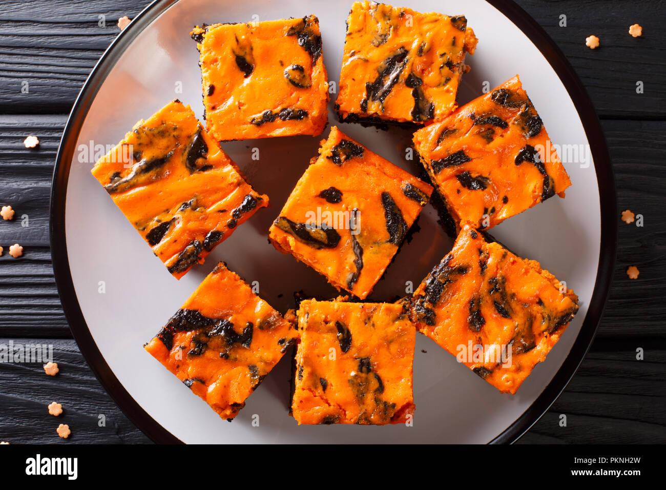 Festliche Halloween köstliche süße Dunkle brownie Kuchen mit orange Kürbis Creme in der Nähe eingerichtet - bis auf einen Teller. Horizontal oben Ansicht von oben Stockbild