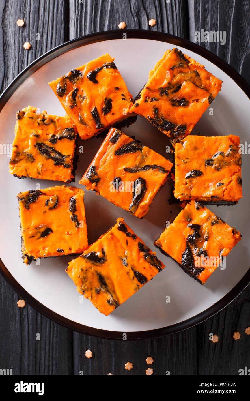 Festliche Halloween köstliche süße Dunkle brownie Kuchen mit orange Kürbis Creme in der Nähe eingerichtet - bis auf einen Teller. Vertikal oben Ansicht von oben Stockbild