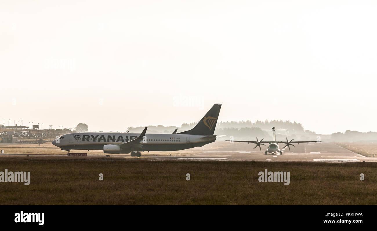 Cork, Irland, 11. Juli 2018. Ryanair Boeing 737 über Weg von der Piste 16/34 für einen Flug nach Lanzarote, während eine Aer Lingus ATR-Flugzeuge zu Ma nehmen Stockbild