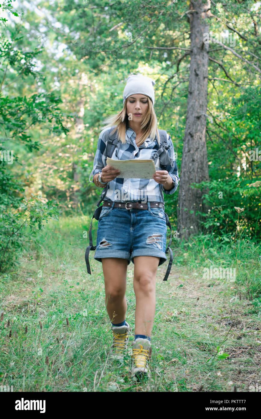 Junge Frau liest Karte im Berg Stockbild
