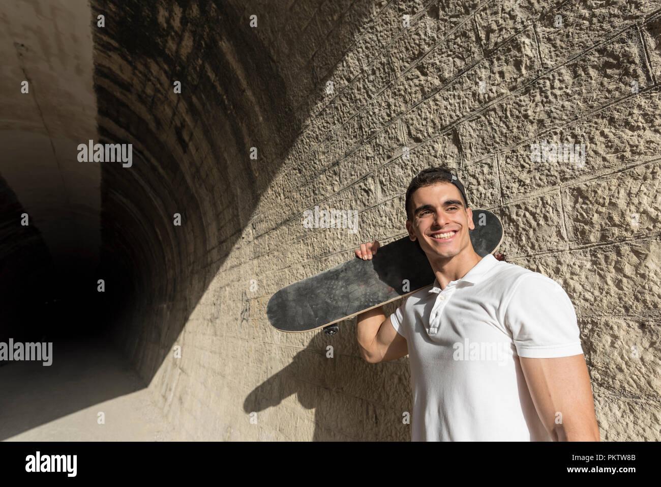 Junger Mann, der in der Tunnelbauweise mit Skateboard posing Stockfoto