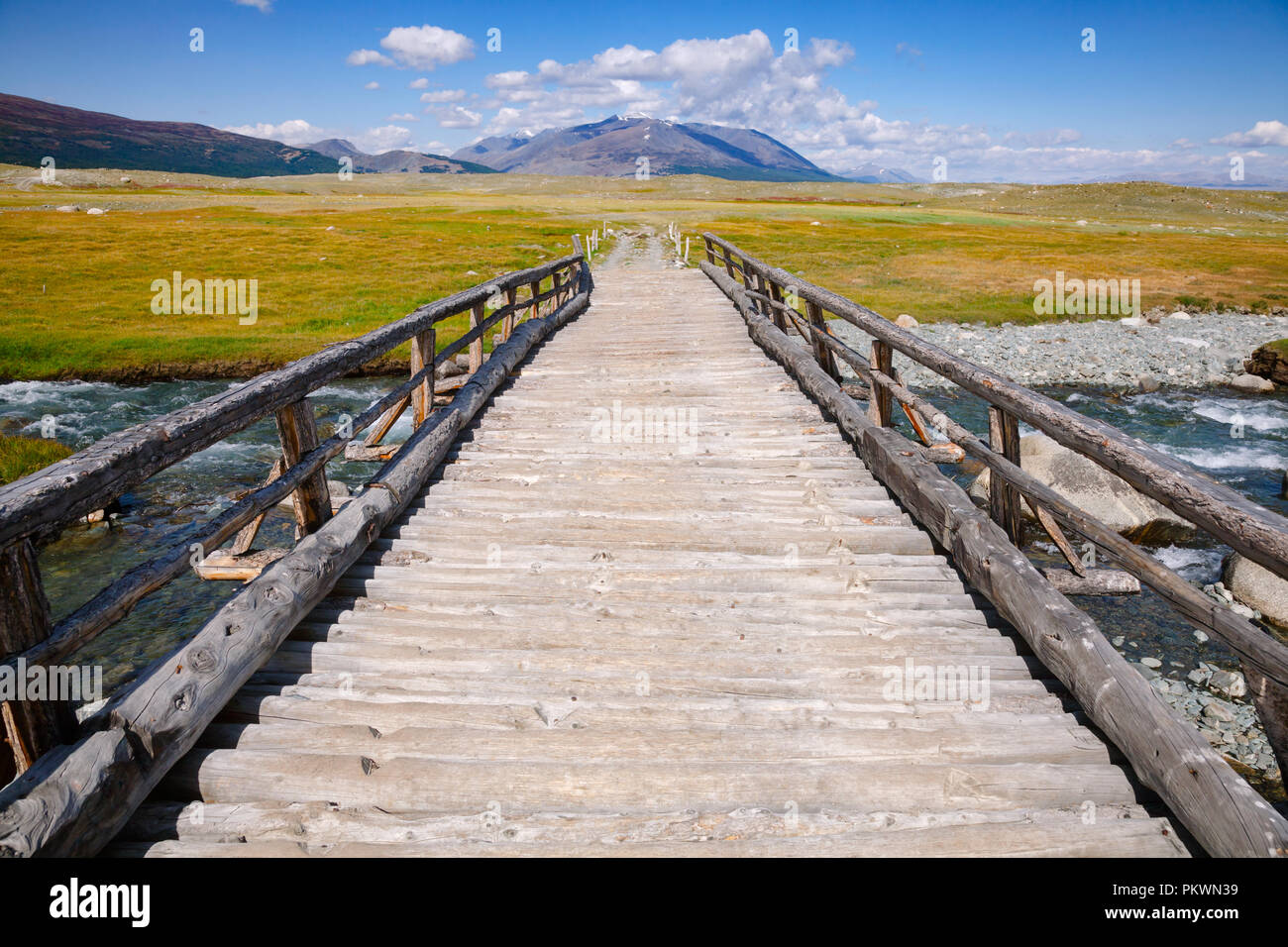 Hölzerne Brücke über einen Fluss mit weit entfernten Bergkette im Hintergrund, Altai Gebirge, der westlichen Mongolei Stockbild