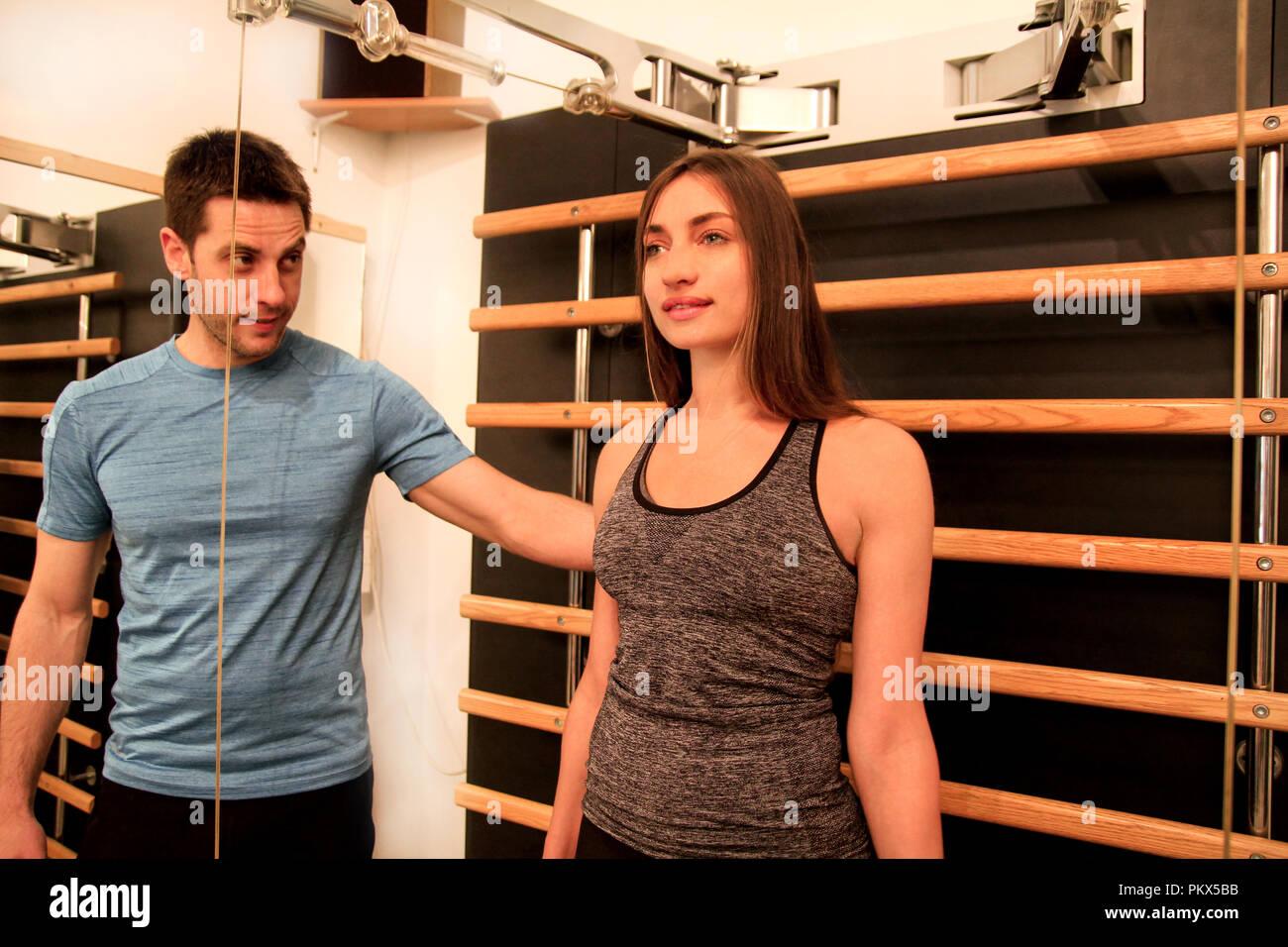 Junge Frau Übung in einer Turnhalle mit Hilfe Ihrer persönlichen Fitness Trainer kinesis Technologie Maschine Träger im Fitness Studio. Sport, Fitness Stockbild