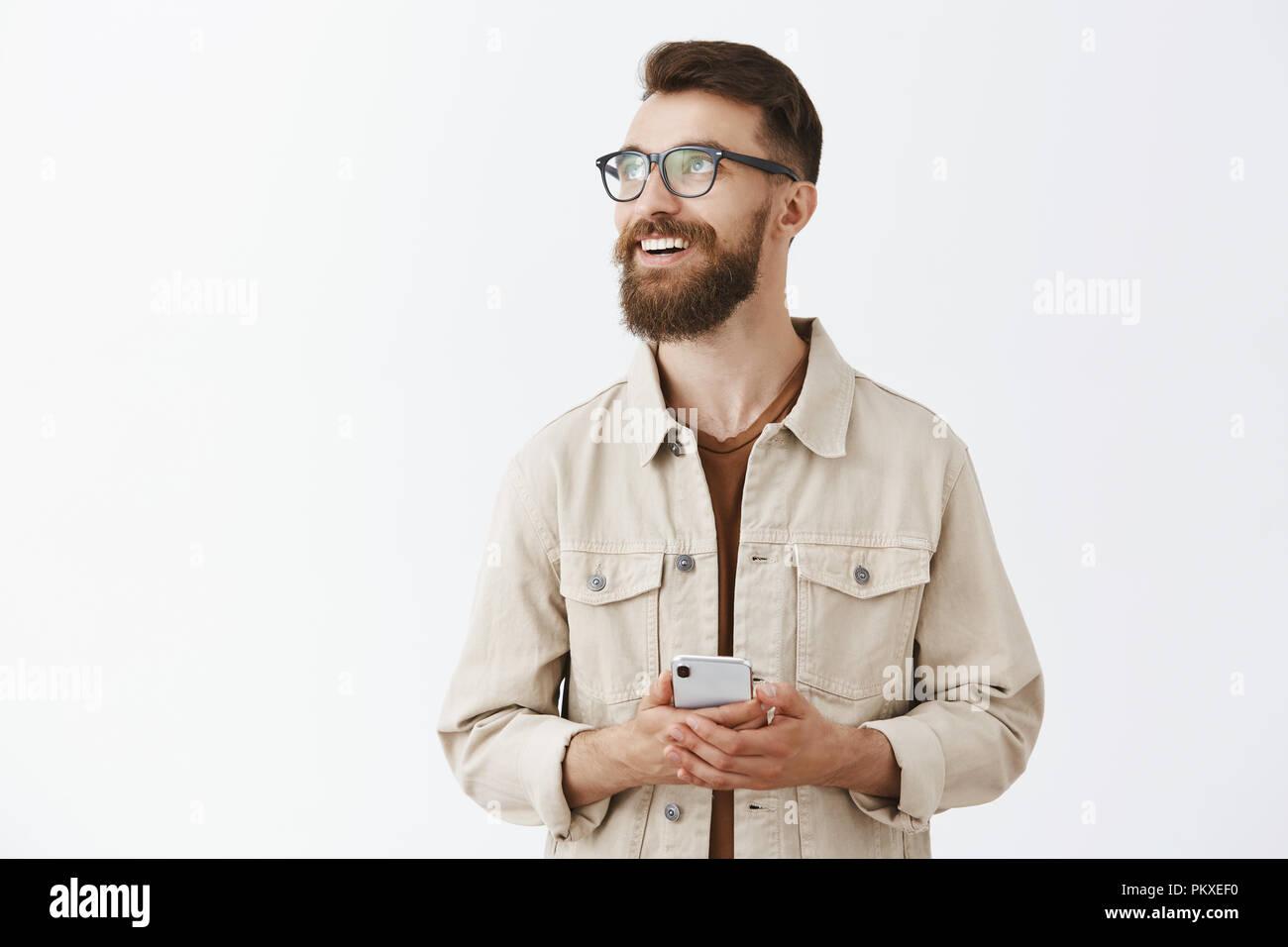 Stilvolle stattliche Städtische nach bärtigen Mann Unternehmer in Gläsern freudig lächelnd auf der Suche an der oberen linken Ecke verträumt und nostalgische Erinnerung an lustiger Moment beim Scrollen Fotoalbum im Smartphone Stockbild