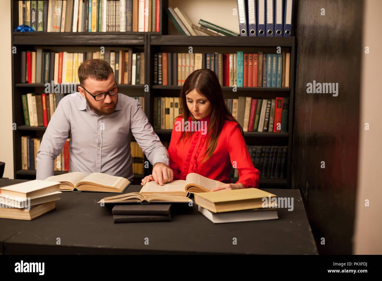 Ein Mann und eine Frau lesen Bücher in der Bibliothek sind die Vorbereitung auf die Prüfung 1. Stockbild
