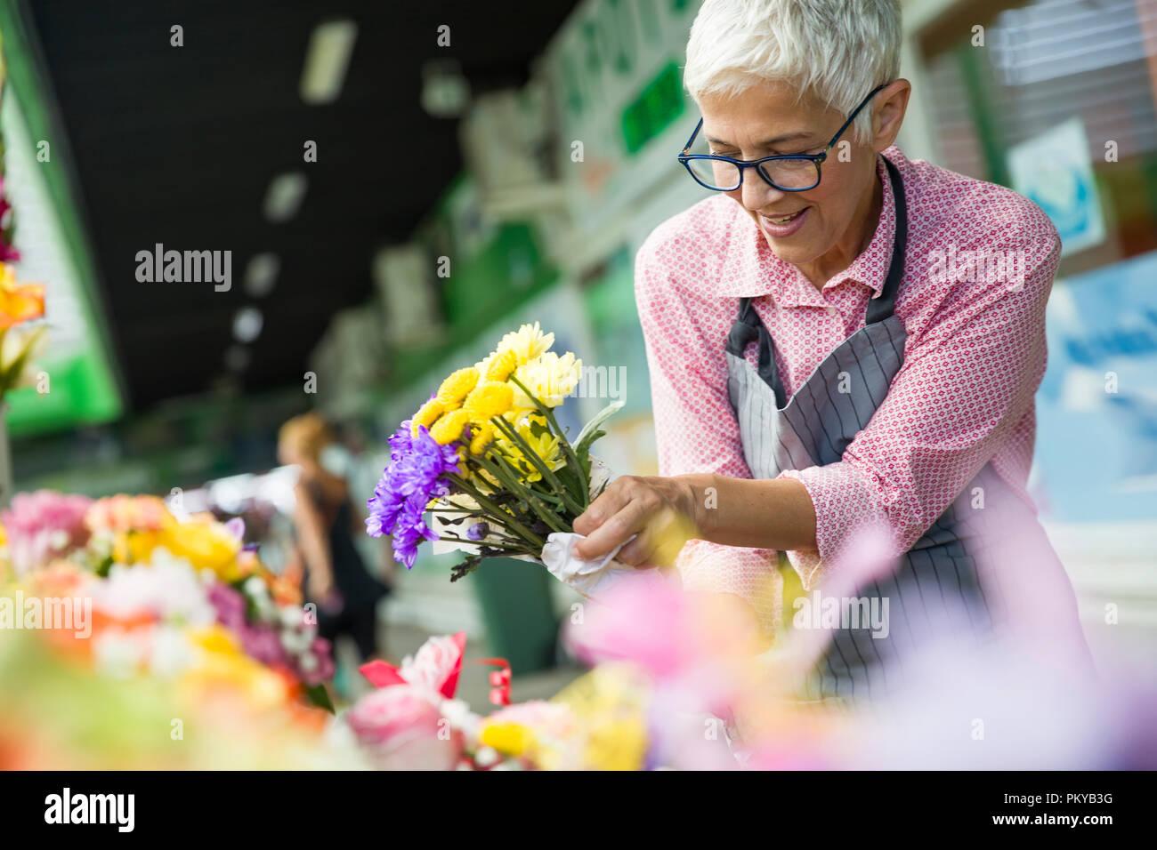 Charrming senior Frau vertrieb Blumen auf dem lokalen Markt Stockbild