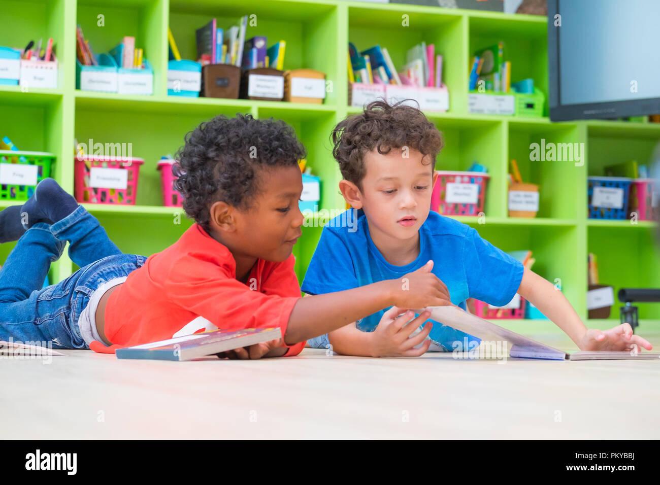 Zwei junge Kind legte sich auf den Boden und lesen Märchen Buch im Kindergarten Bibliothek, Kindergarten Schule Ausbildung Konzept Stockbild