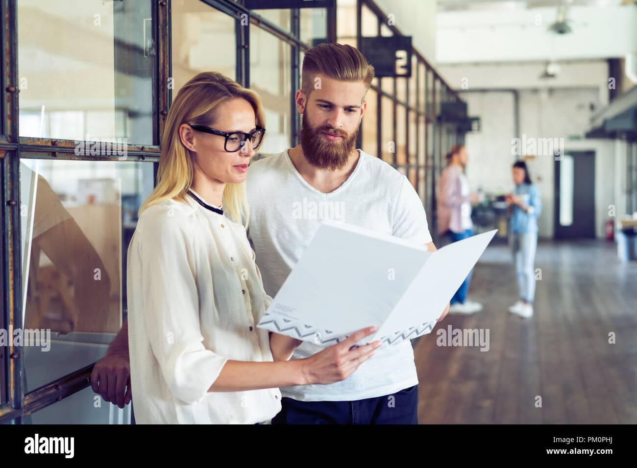 Gemeinsame Nutzung von frischen Ideen. Gruppe junger Geschäftsleute in Smart Casual Wear reden und lächeln beim Stehen im Büro Flur. Stockbild
